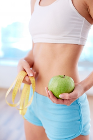 woman measuring: Vertical image of fit female holding green apple in hand