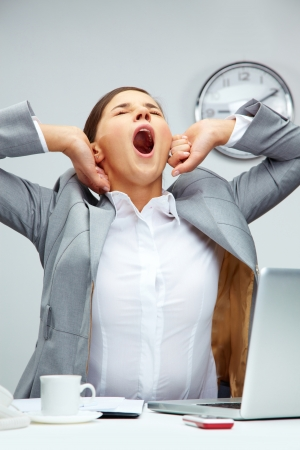 tiredness: Tired office manager stretching herself and yawning