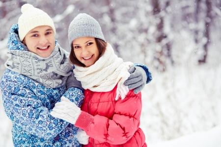 winterwear: Portrait of happy young man embracing his girlfriend in winter park