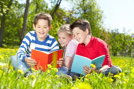 Cute children enjoying reading on a sunny summer day photo