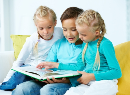 Lovely children looking through a picture book Stock Photo