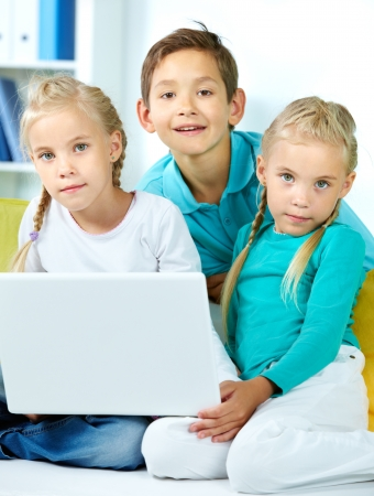Vertical portrait of modern kids using a laptop Stock Photo - 17257598