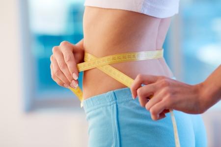 waist: Primer plano de mujer delgada mide su cintura