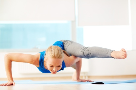 sportwear: Portrait of young woman doing physical exercise in gym