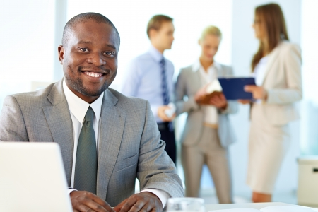 Portrait of happy boss looking at camera in working environment Stock Photo - 17340468