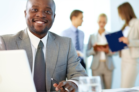 busy office: Portrait of happy boss looking at camera in working environment