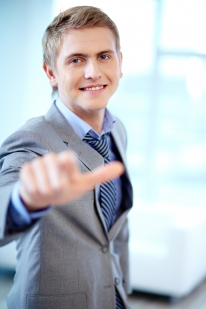 Portrait of cheerful businessman looking at camera while pointing at you photo
