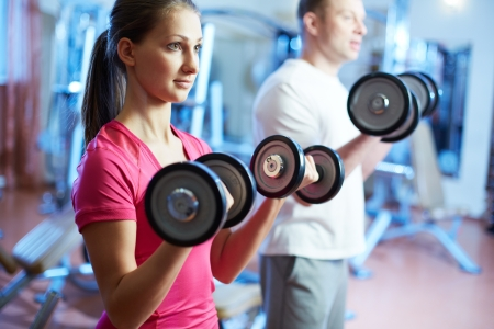Portrait of pretty girl training in gym with young man near by Stock Photo