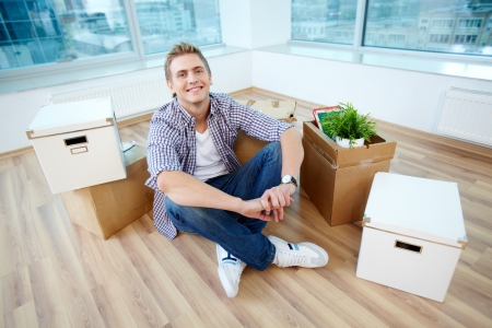 handsome student: A young guy sitting on the floor of new house surrounded with boxes Stock Photo
