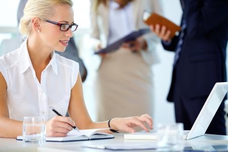mujer sola: Retrato de secretario ocupados mirando port�til mientras en red
