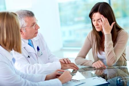 persona sentada: Retrato de dos profesionales de consultor�a paciente con dolor de cabeza en el hospital