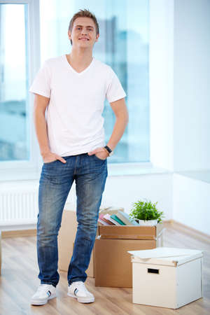 A young guy standing in new flat with boxes near by Stock Photo