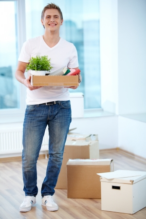 man carrying box: A young guy with boxes looking at camera in new flat