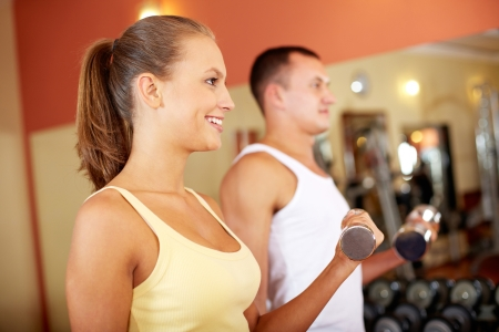 Portrait of pretty girl training in gym with young man near by photo