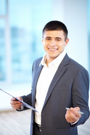 business attire teacher: Portrait of cheerful businessman with clipboard looking at camera Stock Photo