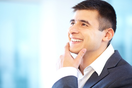 Portrait of cheerful businessman touching his chin photo