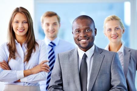 Portrait de leader confiant regardant la caméra avec trois partenaires derrière