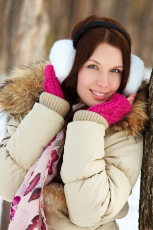 january 1: Portrait of pretty girl standing by tree trunk and looking at camera