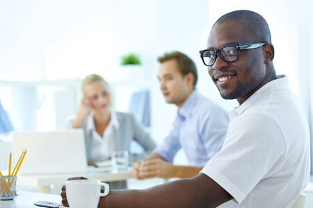 casual business: Portrait of happy African guy looking at camera in working environment