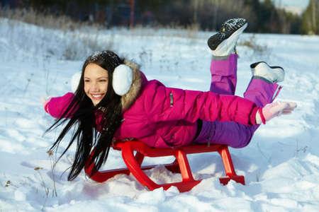 winterwear: Portrait of happy girl lying on snow and enjoying winter