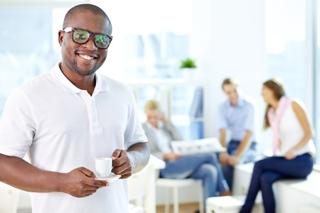 Portrait of happy African guy with cup looking at camera in working environment Stock Photo - 17340407