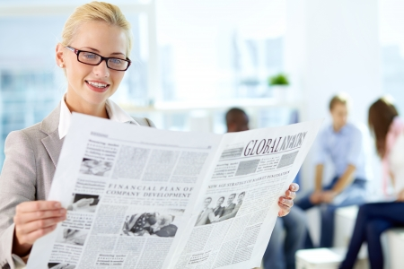 newspaper read: Portrait of happy female reading newspaper in working environment