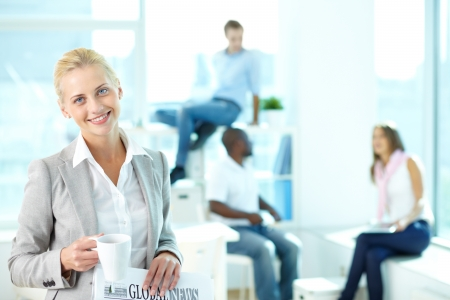 office environment: Portrait of happy female with cup and newspaper looking at camera in working environment