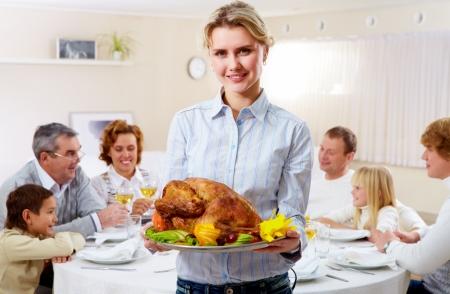 högtider: Porträtt av vacker kvinna med rostad kalkon på bakgrund av lyckliga familjen
