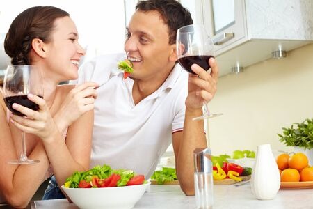 aperitif: Young happy couple eating vegetable salad and drinking red wine