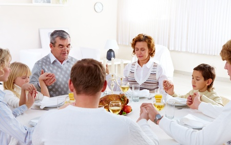 big family: Portrait of big family sitting at festive table and holding each other by hands while praying Stock Photo