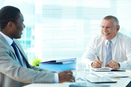 Portrait of senior boss and his employee laughing at meeting Stock Photo - 17340596
