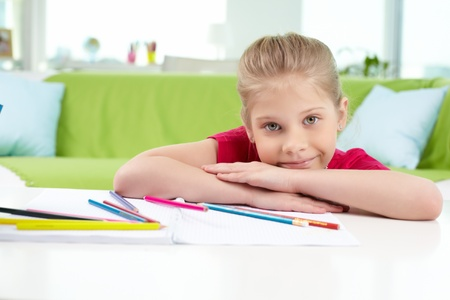 Portrait of lovely girl looking at camera with colorful pencils near by photo