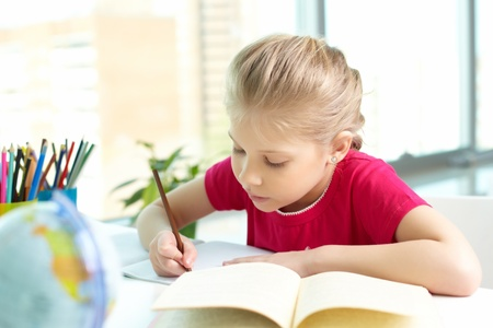 kids learning: Portrait of lovely girl drawing with pencil in copybook