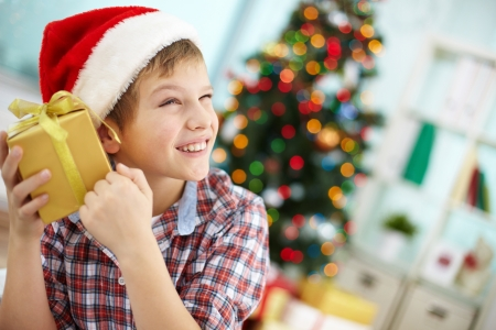 and guessing: Portrait of smiling boy holding giftbox and guessing what is inside on Christmas evening