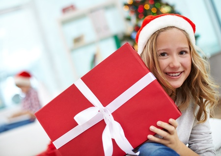 Portrait of happy girl peeking out of big red giftbox on Christmas evening photo
