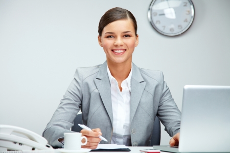 place of work: Image of young employer looking at camera while planning work in office Stock Photo