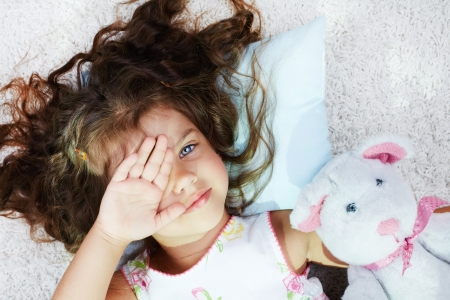 Portrait of lovely girl with teddybear rubbing her eyes after sleep Stock Photo - 17340402