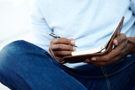 hombre escribiendo: Manos de hombre joven africano escrito algo en libreta