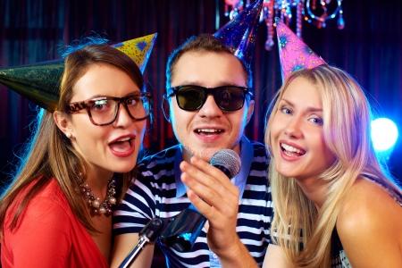 karaoke bar: Portrait of happy friends singing in microphone in the karaoke bar