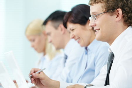 training course: Business people sitting in a row and working, focus on successful young man Stock Photo