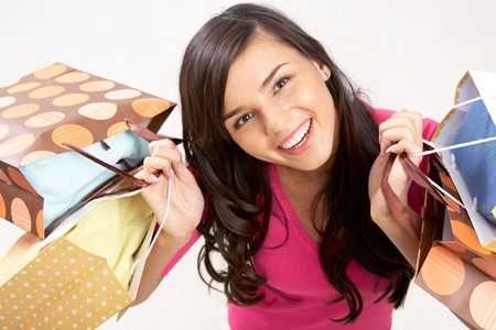 Portrait of happy girl with colorful paper bags looking at camera with smile  Stock Photo - 17343317
