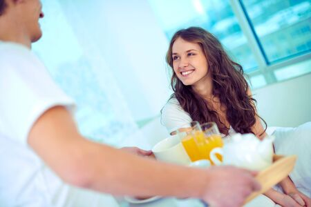 lovely couple: Happy female looking at her husband holding tray with breakfast Stock Photo