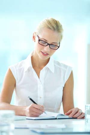 diligente: Tiro vertical de un diligente secretario toma notas
