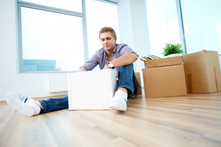 A young guy sitting on the floor of new house and unpacking box photo