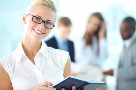 secretaria: Retrato de la secretaria ocupado con la libreta mirando a la cámara en el entorno de trabajo