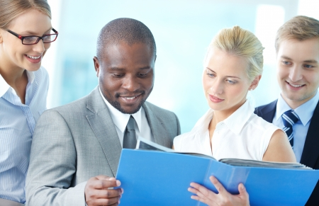 Portrait of confident employees looking at document at meeting Stock Photo - 17381048