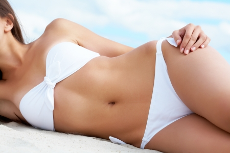 young bikini: Torso of luxurious woman in white bikini sunbathing