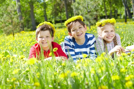 Three children with dandelion wreaths having rest on grass  Stock Photo - 17381005