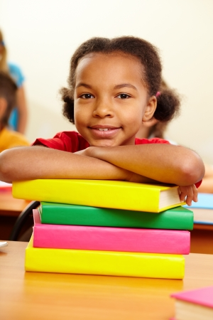 Portrait of lovely girl with stack of books looking at camera at workplace Stock Photo - 17380684
