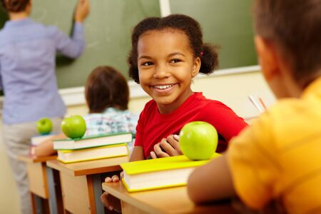 Portrait of cute girl looking at classmate at lesson photo